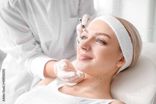 Obraz Young woman undergoing eyebrow correction procedure in beauty salon - fototapety do salonu
