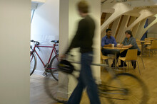 Office Life And Interiors. Man With Bicycle And Two Office Workers In Background.
