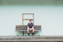 Teenage Boy Sitting Alone On A Wooden Bench Seat