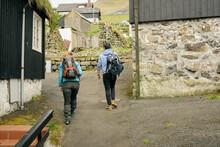 Unrecognizable Travelers Walking In Village