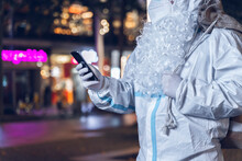 Photo Of A Person With The Coverral For The Covid 19 , The Beard Of Santa Claus, And The Bag Of Gifts, Looking At The Phone. In The Background The Empty And Desolate City.