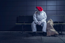 Photo Of A Beggar, Dressed In The Coverall Used Against The Coronavirus, The Mask, And The Beard And Hat Of Santa Claus, Sitting On A Bench In Town. COVID Concept.