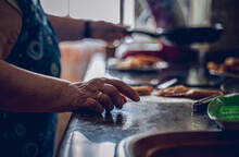 Photos Of Details, Of An Old Lady, In A Typical Grandmother's Kitchen, In Spain, While She Is Cooking. In The Foreground The Hand With The Wedding Ring, In The Background The Hand Holding The