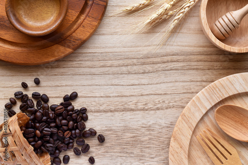 Valokuvatapetti Top view wooden table, Natural wooden kitchen utensils lined up on the sides with coffee beans and dry ear of rice