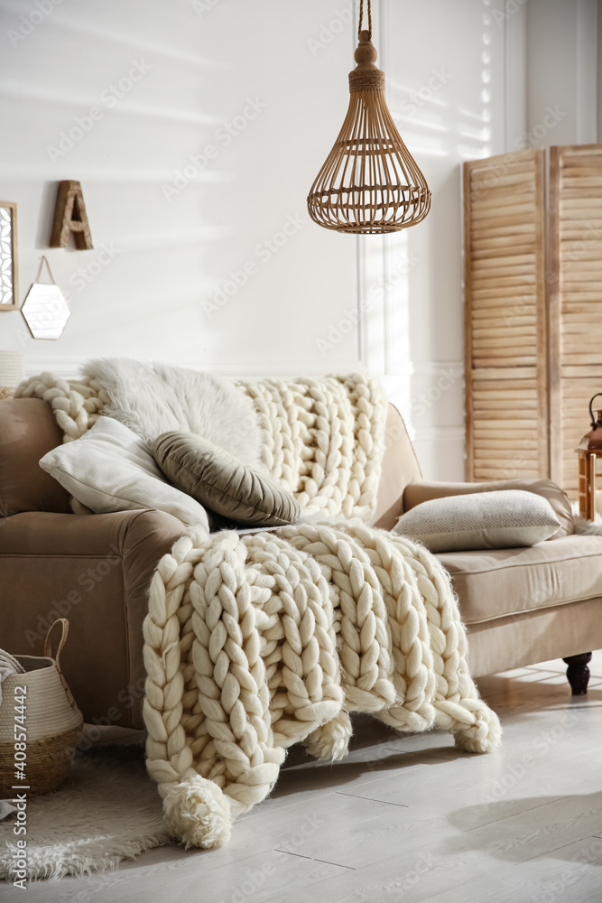 Fototapeta Cozy living room interior with beige sofa, knitted blanket and cushions