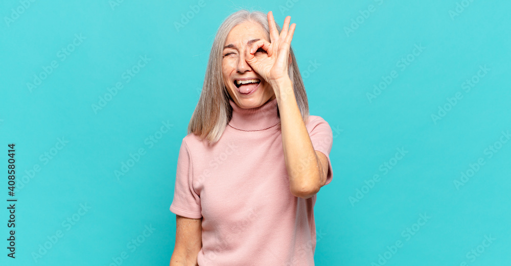 Fototapeta middle age woman smiling happily with funny face, joking and looking through peephole, spying on secrets