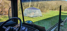 View Of An Anti Mosquito Tent In A Recreational Or Camping Area From Behind The Windshield Of A Big Bus Or Caravan. Sunny Day.