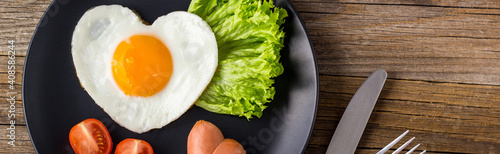Fototapeta banner of Valentines day breakfast with heart shaped fried eggs served on grey plate. obraz