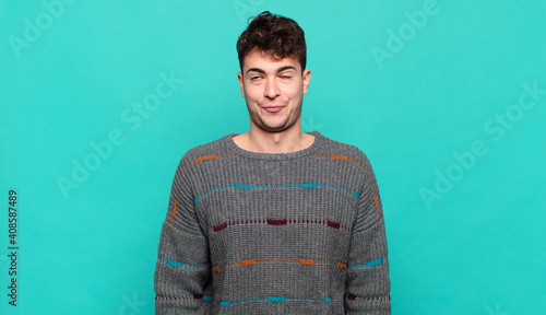Fototapeta young man looking goofy and funny with a silly cross-eyed expression, joking and