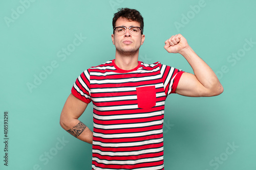 Canvas Print young man feeling serious, strong and rebellious, raising fist up, protesting or