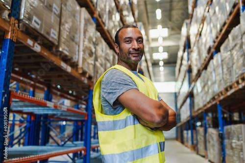 Obraz na plátně handsome warehouse worker wearing security vest posing arms crossed in a warehou