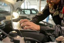 Hands Of Middle Aged Male Worker Of Car Maintenance Service Using Laptop