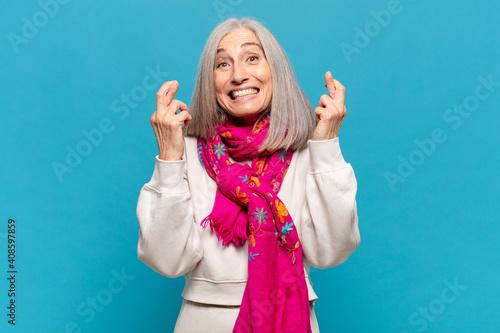 middle age woman feeling nervous and hopeful, crossing fingers, praying and hopi Fototapeta