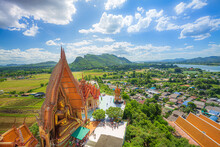 A View From The Top Of The Pagoda, Golden Buddha Statue With Rice Fields And Mountain, Tiger Cave Temple (Wat Tham Seua) Thai And Chinese Temples In Kanchanaburi Province.
