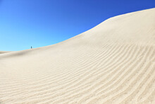 A Minimalism Of A Tiny Person At White Sandy Dunes And Clear Blue Sky