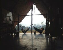 People Relaxing On Hammock In Hut