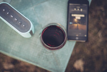 High Angle View Of Wine Amidst Bluetooth Speaker And Smart Phone On Table