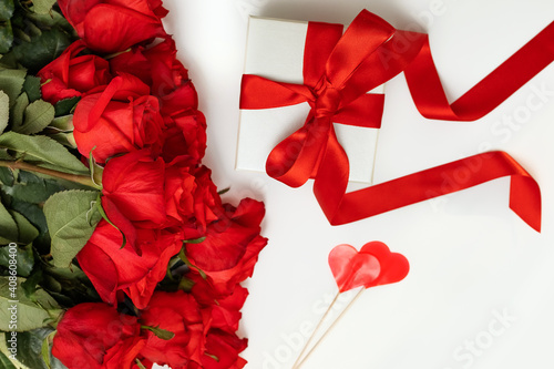Obraz bright scarlet bouquet of roses, gift box with a bright ribbon on a white background with a place for text, greeting card concept happy Valentine's day, March 8, happy birthday - fototapety do salonu