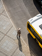 High Angle View Of Man Standing On Sidewalk In City