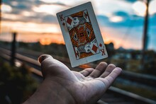 Close-up Of Hand Catching King Card Against Sky During Sunset