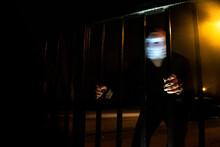 Man Wearing Mask Holding Gate Outdoors At Night