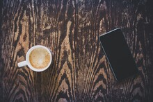 High Angle View Of Coffee By Mobile Phone On Wooden Tables