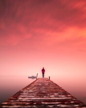 Rear View Of Woman Standing On Pier Over Sea Against Romantic Sky