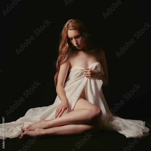 Canvas Print Gloomy portrait of beautiful young sad girl against black background