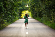 Rear View Of Woman Running On Road Amidst Trees