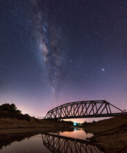 Milky Way And Scenic View Of Bridge Against Sky At Night