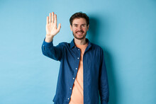 Friendly Young Man Smiling And Raising Hand Up For High Five, Waiving To Greet Or Say Hello, Standing On Blue Background