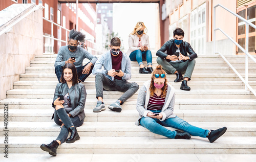 Obraz Urban milenial people using mobile phones covered by face mask on Covid third wave - Worried guys and girls watching video on smartphone - University students sitting at study break - Bright filter - fototapety do salonu