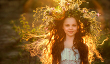 Cute Smiling Little Girl  With Flower Wreath On The Meadow At The Farm. Portrait Of Adorable Small Kid Outdoor.