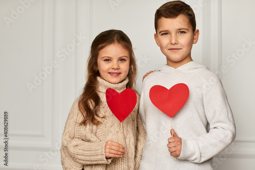Tablou Canvas Happy couple little girl and boy with red hearts against white wall
