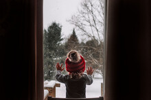 Little Girl Looks Out The Window During A Snow Day In The Winter