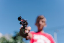 Blonde Teenager Wearing A Red T - Shirt Pointing With A Gun.