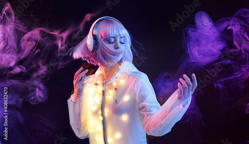 Fotografija Beautiful woman with purple hair in futuristic costume over dark background