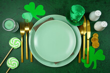 Happy St Patrick's Day Plates Table Setting, Styled With Leprechaun Hat, Shamrocks, And Chocolate Gold Coins, On A Textured Green Background. Mockup. Top View Flat Lay. Copy Space.
