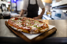Fresh Flatbread Pizza Topped With Pepperoni Cheese And Tomato Sauce