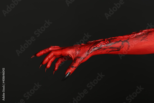 Canvas Print Scary monster on black background, closeup of hand