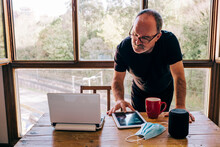 Mature Man Working With Laptop At Home