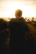 Portrait Of A Man With A Green Jacket On A Vineyard During Sunset