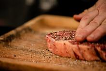 Raw Steak Being Seasoned On A Wooden Board
