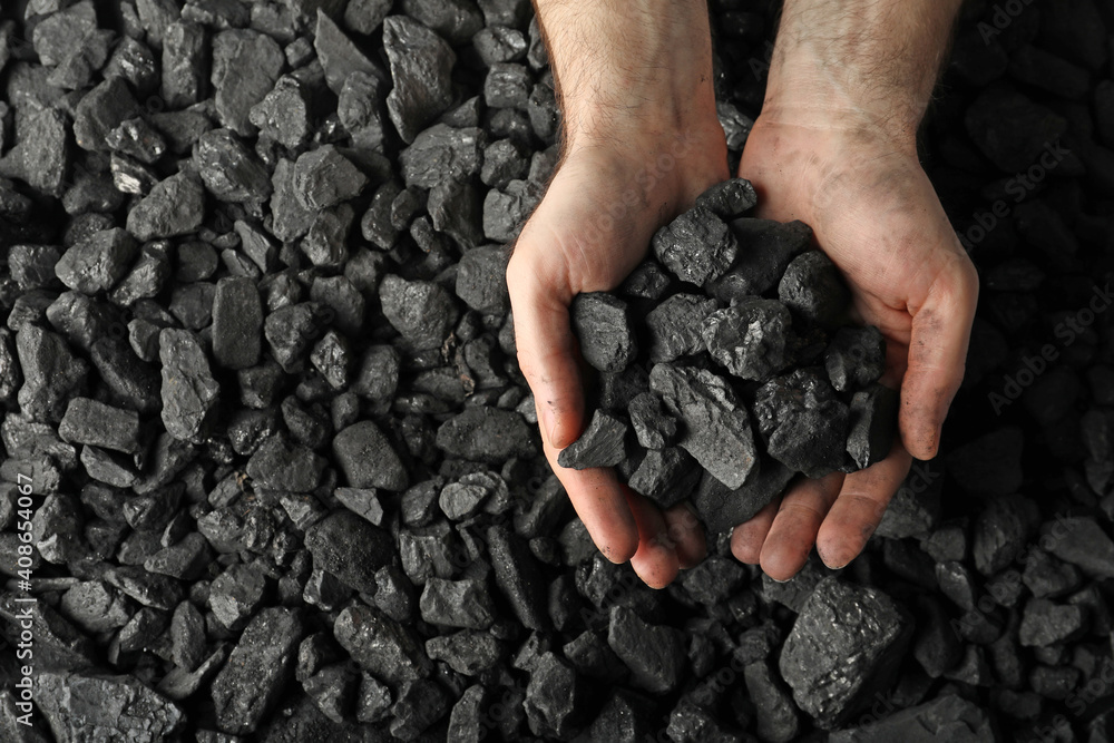 Fototapeta Man holding coal in hands over pile, top view. Space for text