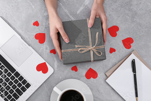 Woman with gift box at light grey marble table, flat lay. Valentine's day celebration