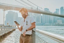 Young Man By River Wearing Face Mask With Phone.
