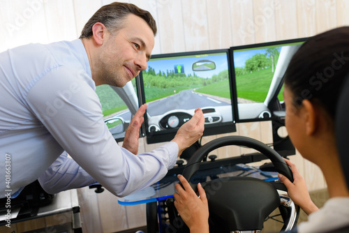 Obraz na plátne driving student being assisted in driving on a simulator