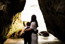 Mother & Son Embracing Looking Out Into Ocean On Beach In San Diego