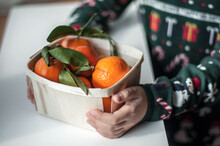 Fresh Tangerines On Twigs With Leaves In A Basket In Child's Hands.