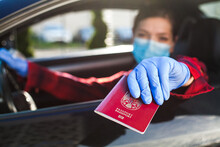 Woman Holding Red Passport Through Car Window